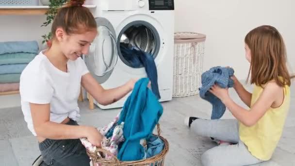 Lányok játszanak mosás előtt ruhák
