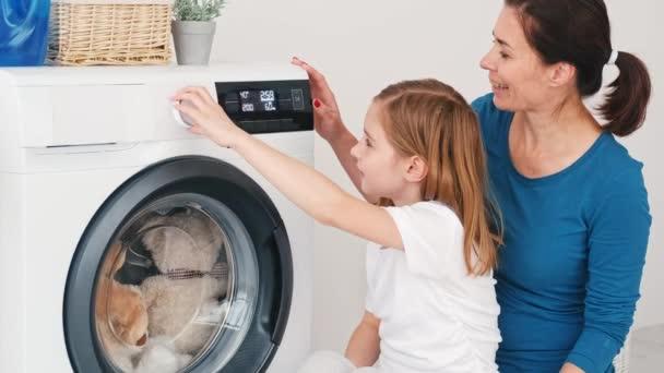 Anya tanítás lánya működteti mosógép