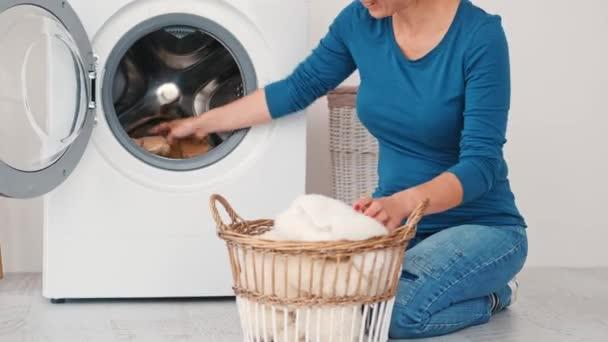 Frau lädt Spielzeug in Waschmaschine