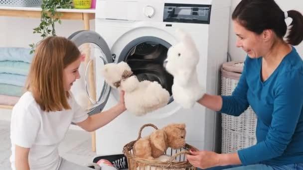 Anya és lánya játékokat pakolnak a gépbe.