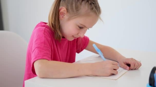 Általános iskolás lány írás tankönyvbe tollal
