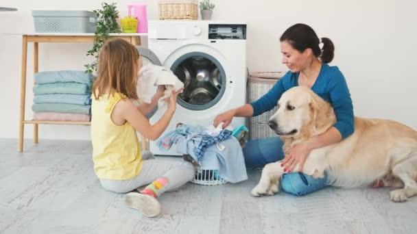 Kleines Mädchen mit Frau beim Wäschewaschen