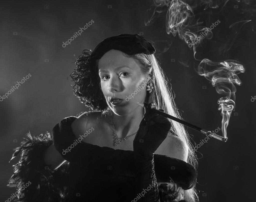 glamorous 1940s film noir woman smoking cigarette � stock