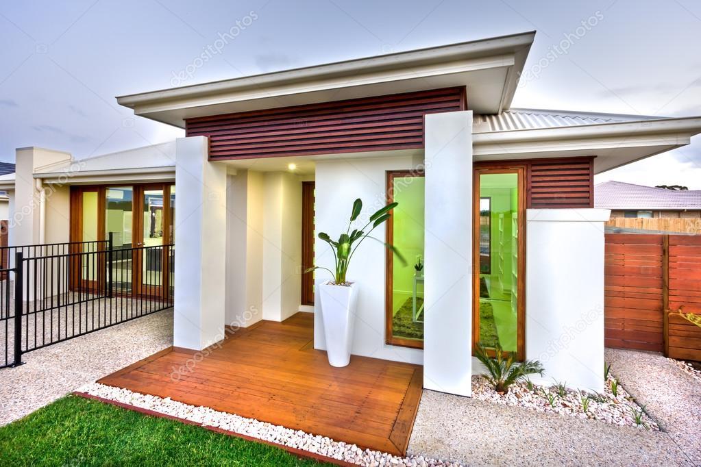 De ingang van het moderne huis met een houten en betonnen werf met