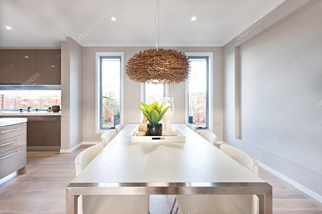 Interieur van een moderne eetkamer met een lange witte tafel en bam ...