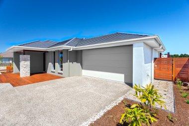 Modern house with a garage and backyard area and blue sky