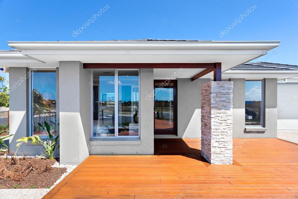 Buitenkant van een modern huis met een houten vloer met blauwe lucht