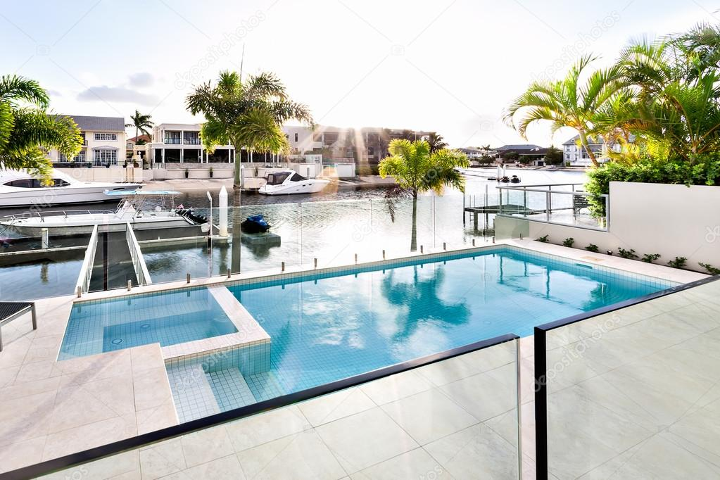 Entertainment Area Of A Modern Multi Million Dollar Home An Infinity Pool Over Looking The Canal As The Sun Goes Down Stock Photo Image By C Jrstock1 103858920