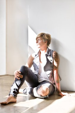 Woman with tattoo sitting on the floor and looking away