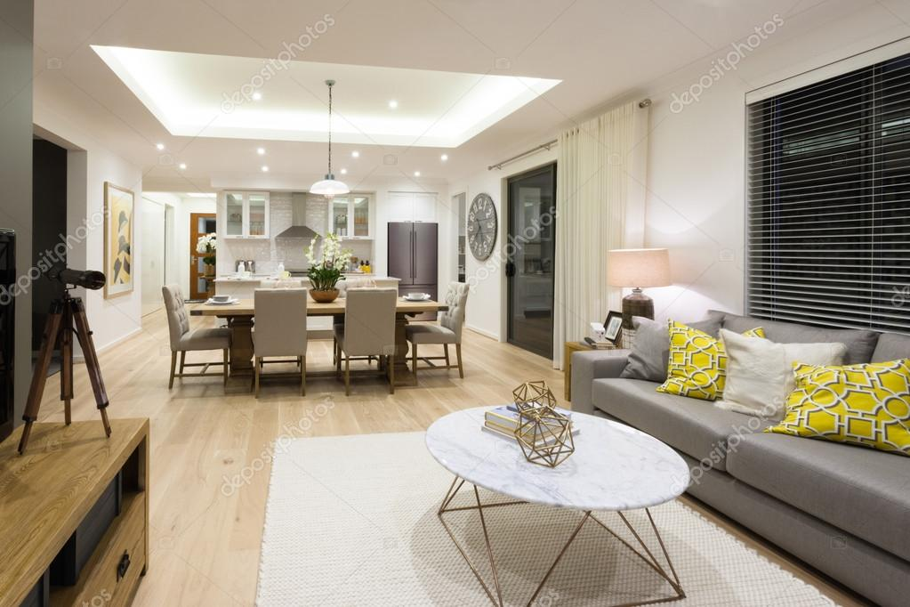 Moderne woonkamer met inbegrip van banken en tafels naast keuken ...