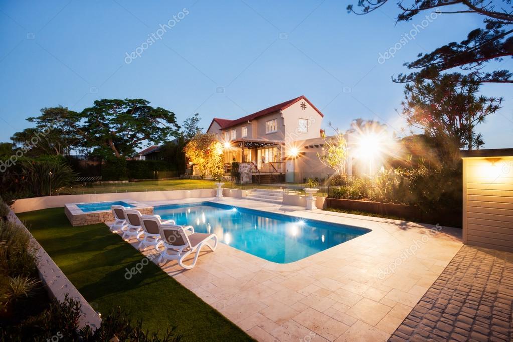 Casa e un giardino con una piscina illuminare con luci u foto