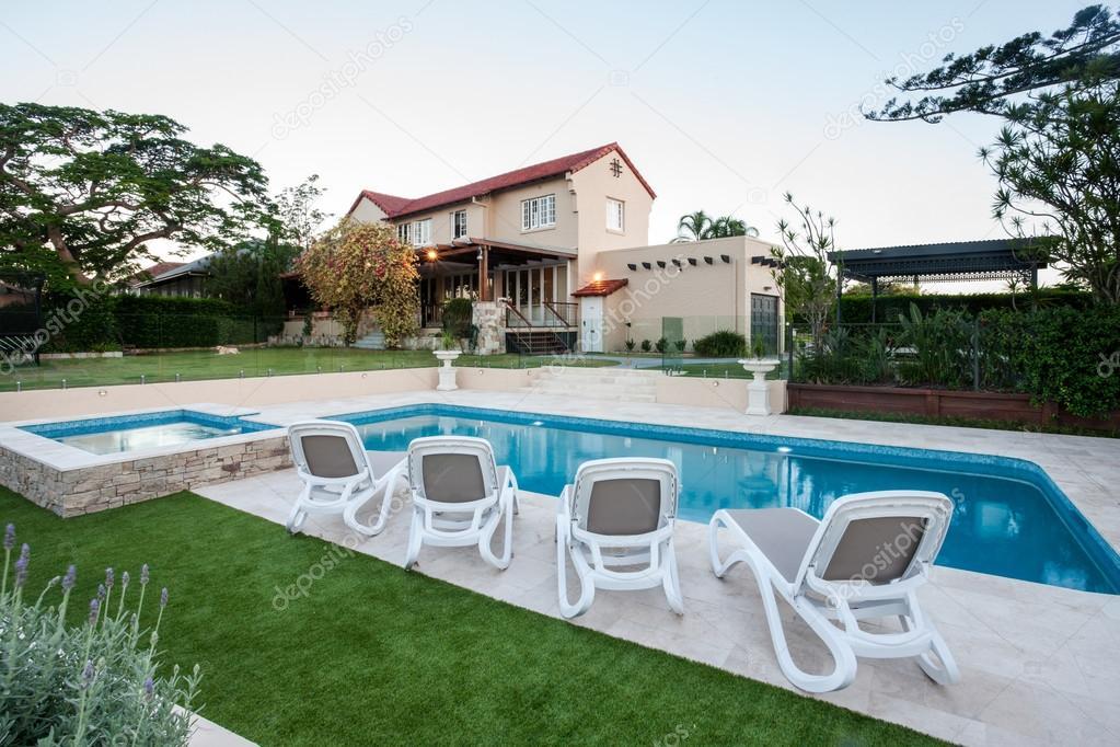 Moderna piscina davanti alla casa con un prato foto for Casas modernas con piscina