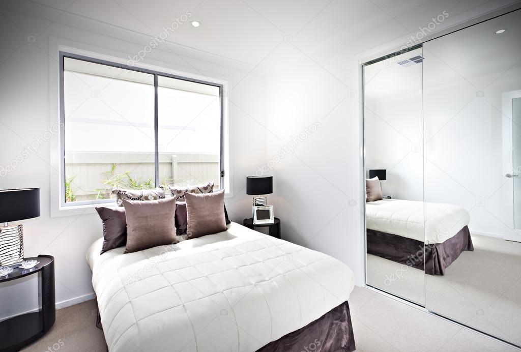 Klassieke slaapkamer met windows en lampen naast een spiegel ...