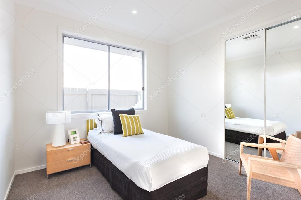 Moderne slaapkamer met een eenpersoonsbed en witte lakens in de ...