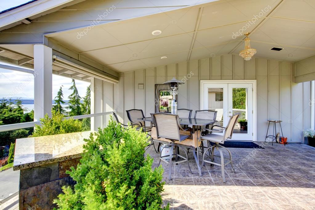 Grande terrasse couverte avec table en verre et porte en ...