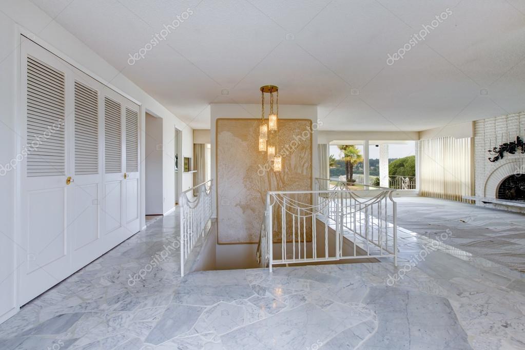 Ongemeubileerde hal en woonkamer met witte omheind trap
