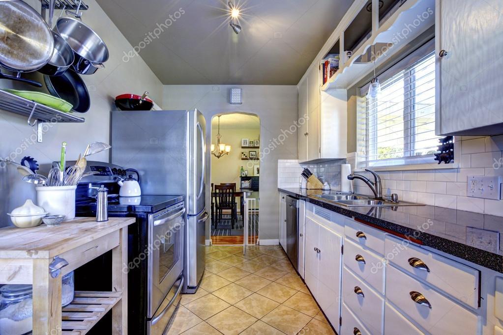 Interiore della cucina blu con piastrella marrone e un frigorifero