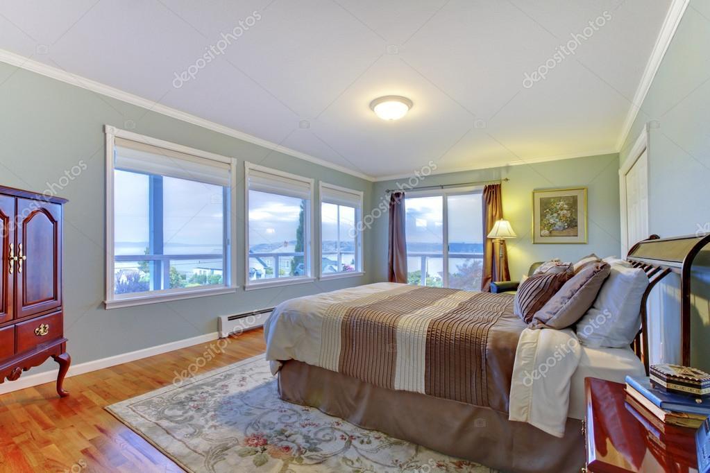 Luxury Home Master Bedroom With Blue Walls, Large Brown Bed And Hardwood  Floor. U2014