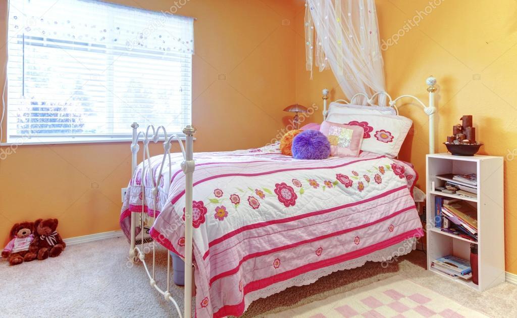 oranje meisje tiener kinderen slaapkamer met speelgoed witte bed frame en stockfoto