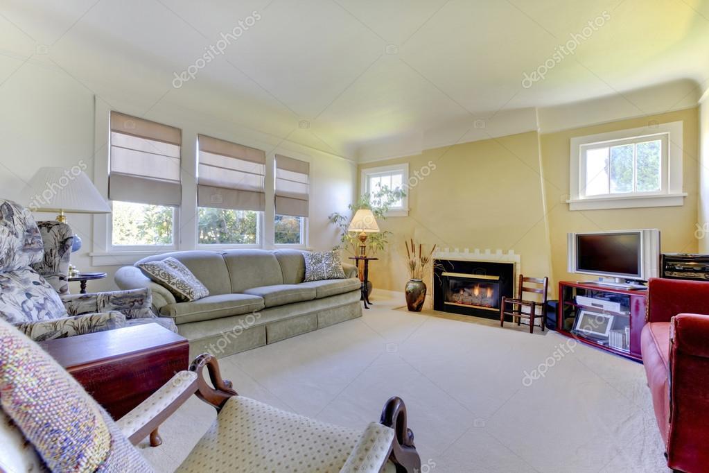 Gezellige woonkamer met tapijt vloer, gele wanden en open haard ...