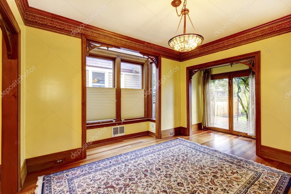 Elegante lege woonkamer met gele muren, gesneden houten deuren ...