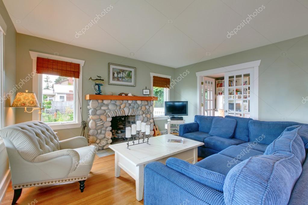 Klassieke Amerikaanse woonkamer met blauwe sofa en open haard ...