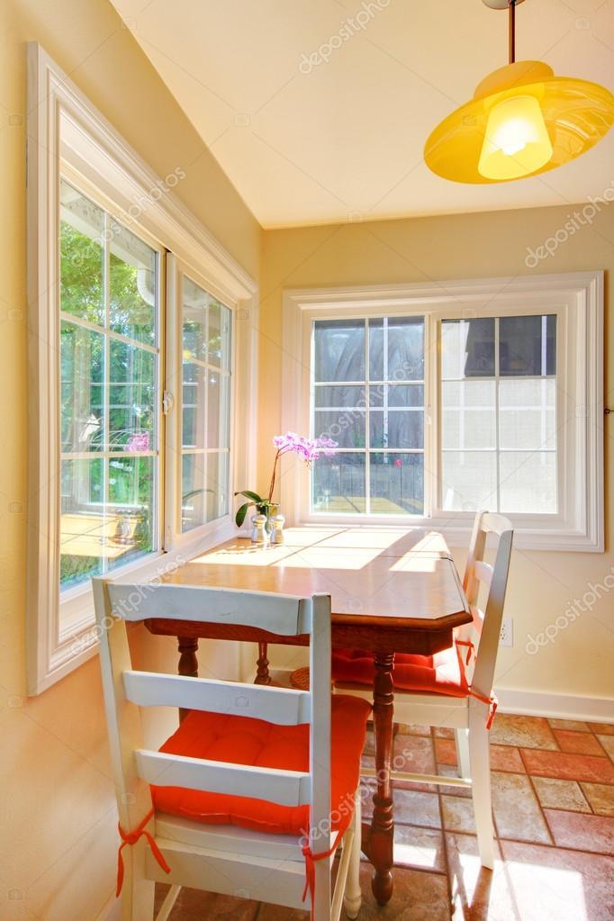 Brillante comedor pequeño con piso de baldosas y grandes ventanas ...