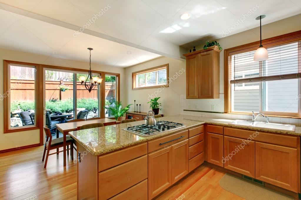 Sala de cocina blanco y marrón con piso de madera, armarios y zona ...