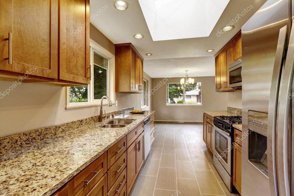 Sala cocina con gabinetes de marrón mates, tapas del granito ...