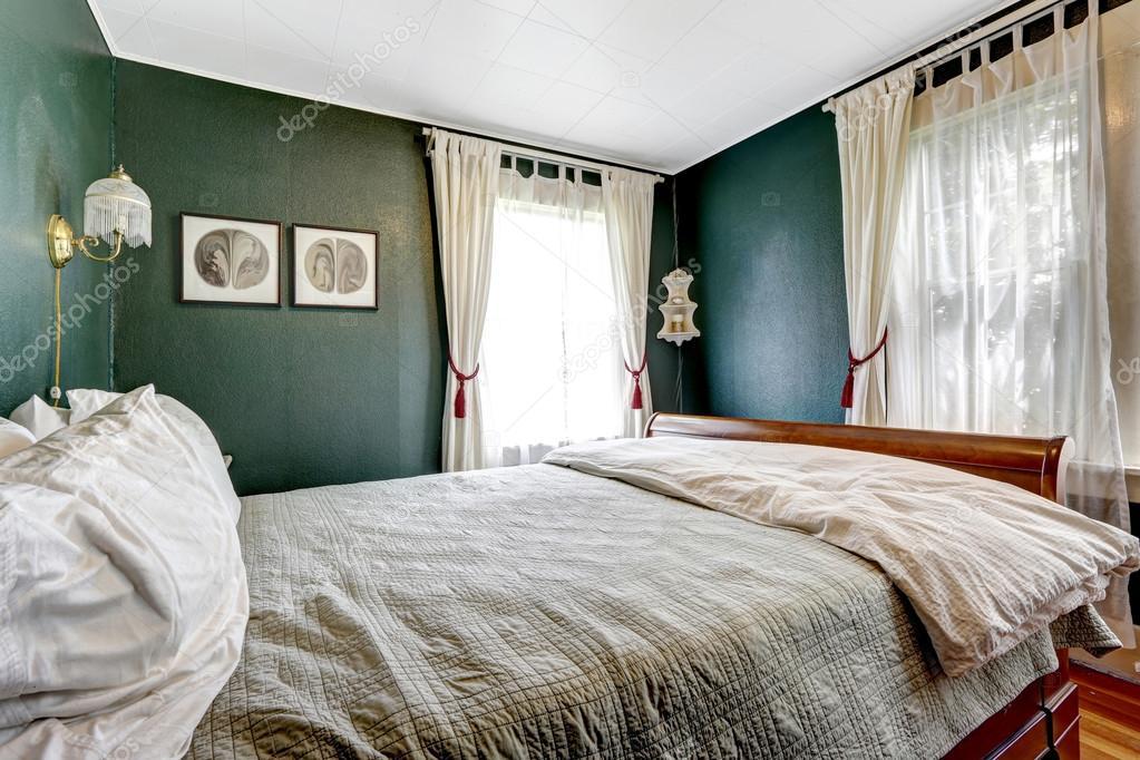 Piccola camera da letto con letto in legno, pareti verde scuro ...