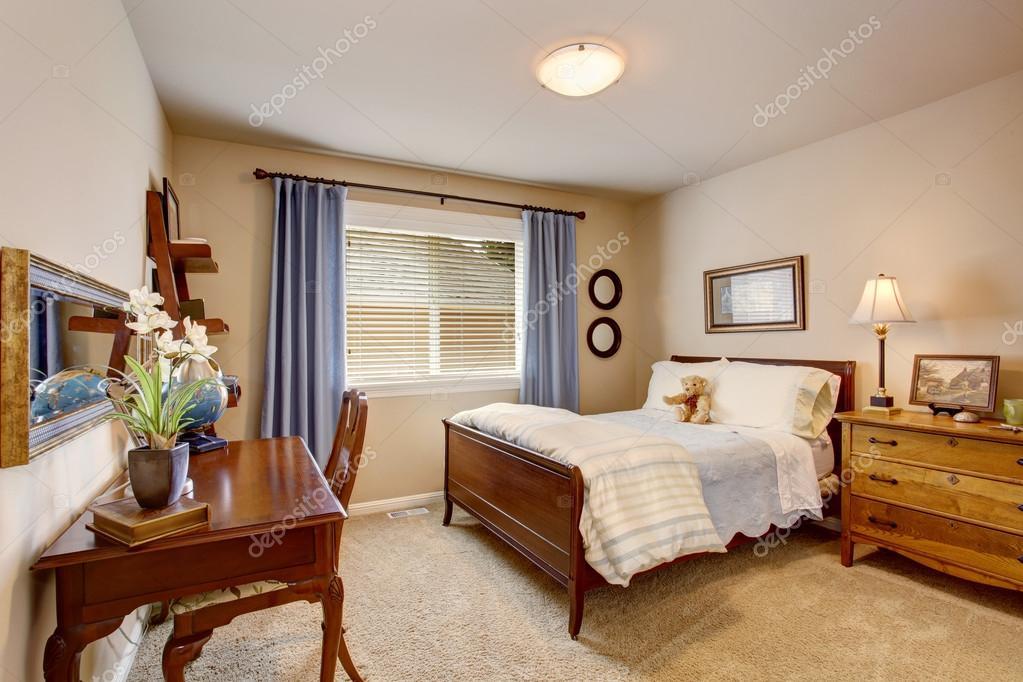 Chambre d\'enfant beige avec des meubles en bois situé, rideaux bleu ...