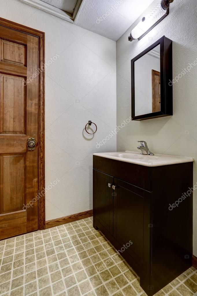 Simple Bathroom Interior With Black Cabinets And White Sink Stock