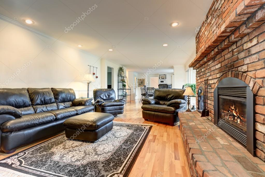 Luxury Living Room Interior With Black Leather Sofa Set And Brick Fireplace Stock Photo