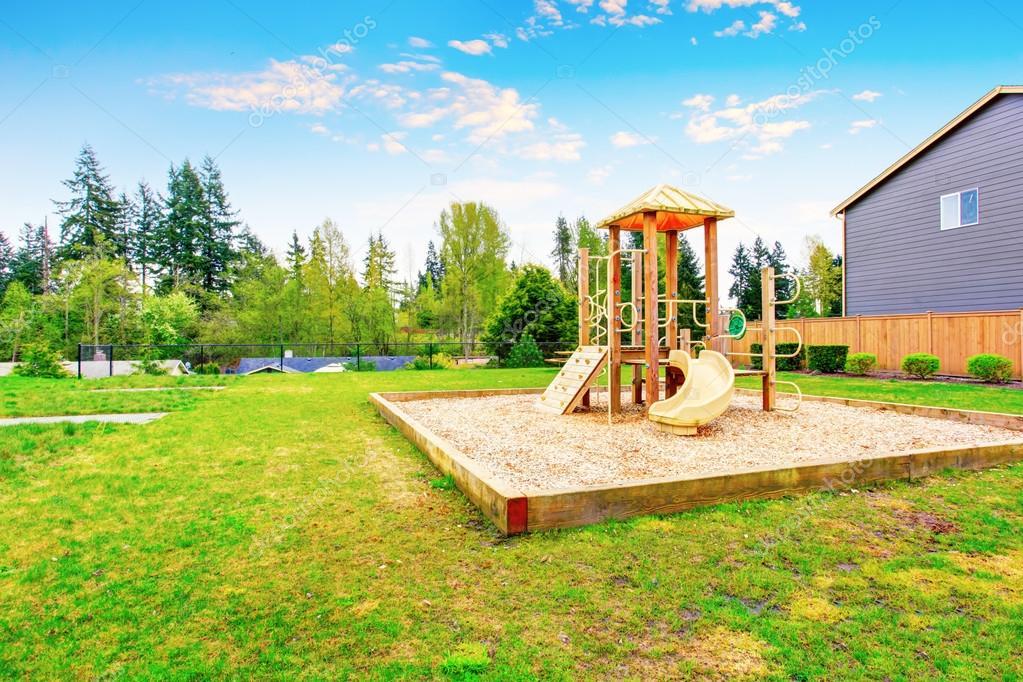 rea de patio trasero con juego de madera para nios con columpios y toboganes u foto