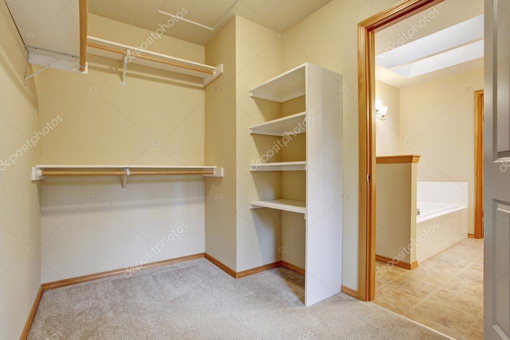 Vuoto e cabina armadio con ripiani in legno, pavimento in moquette ...