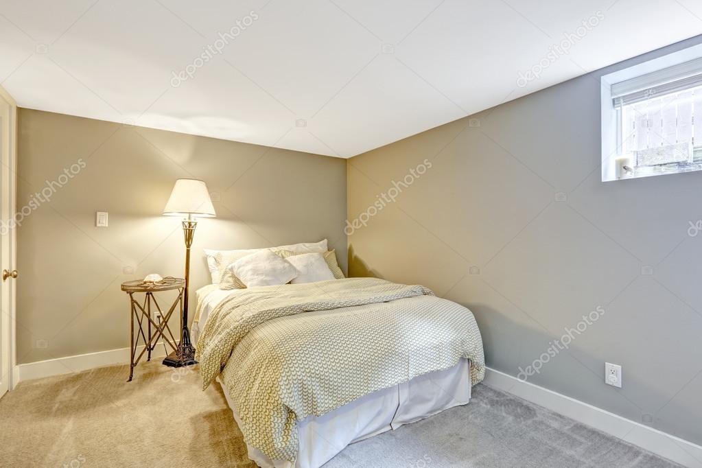 Piccola camera da letto in tonalità di grigio luce con lampada da ...