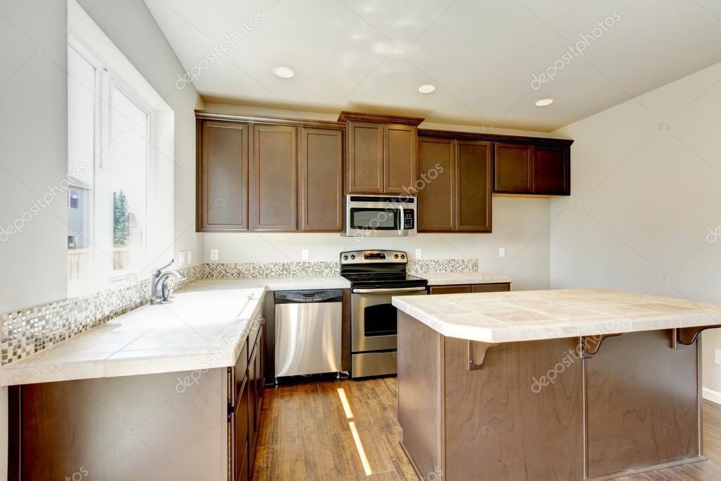 Piccolo ma pratico cucina con mobili marrone e top in marmo