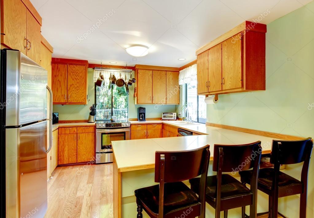 Lichte keuken met licht bruin kasten en oude houten krukjes