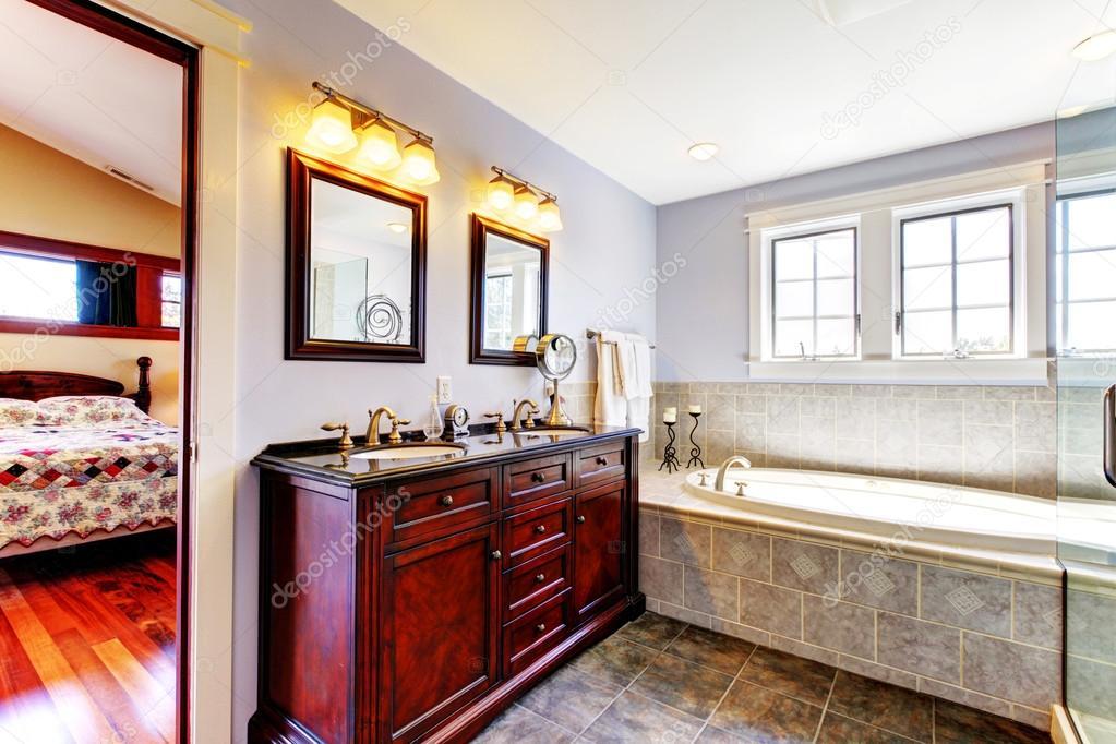 Mooie lavendel badkamer met bad en houten kast met twee