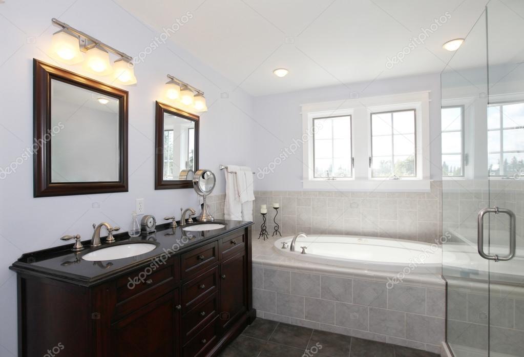 Badkamer met bad en houten kast met twee spoelbakken u stockfoto