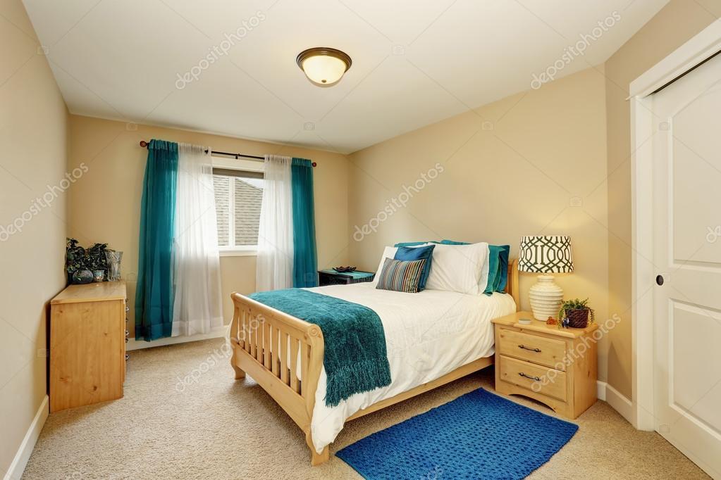 Propre chambre beige avec rideau turquoise et lit en bois ...
