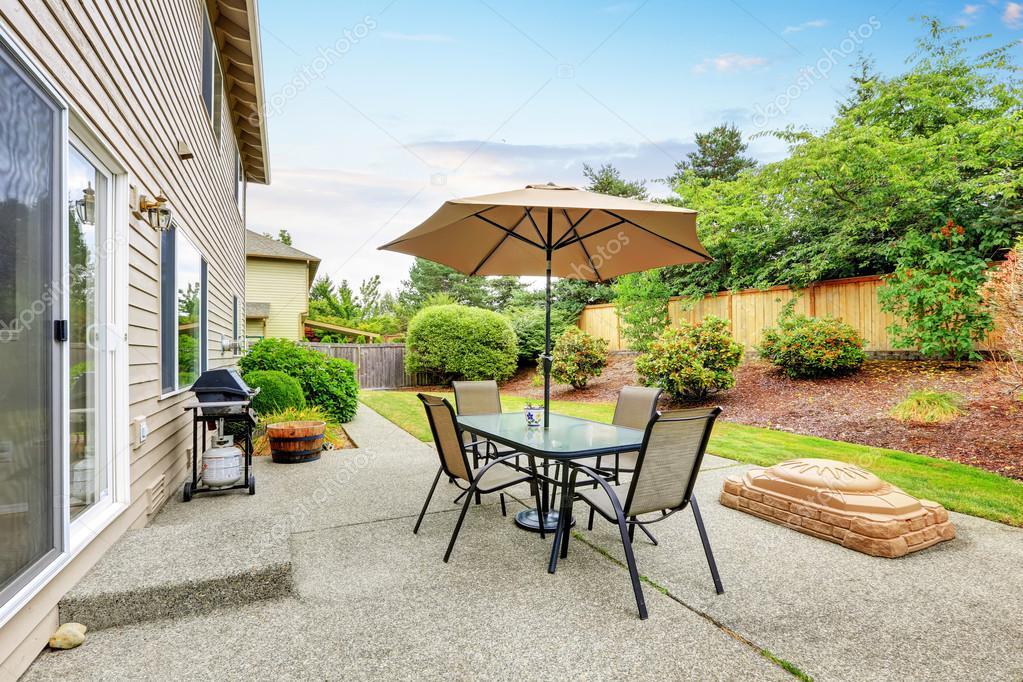 Patio Table Set With Umbrella In The Back Yard. U2014 Stock Photo