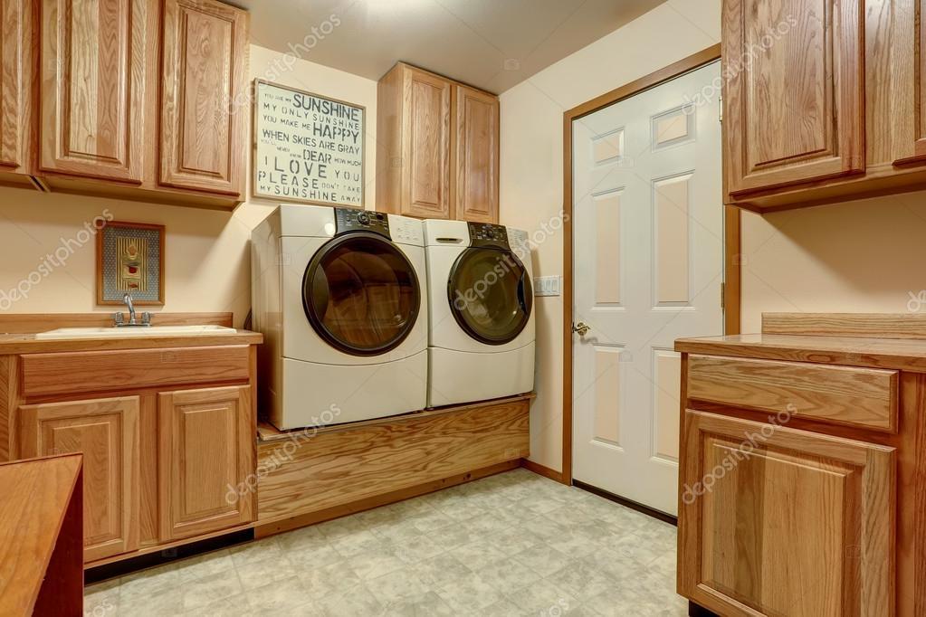 Lavanderia con armadi in legno e pavimento di piastrelle u foto