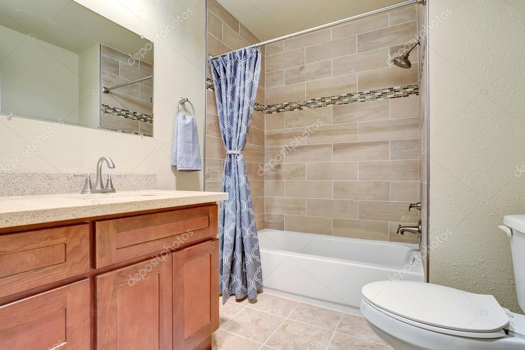 Interior de cuarto de baño con cortina de ducha azul y gabinete de ...
