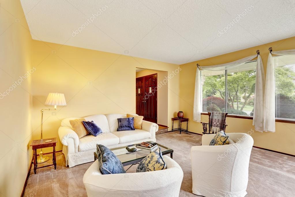 Gezellige woonkamer met lichte gele muren en witte meubels Gezellige woonkamer