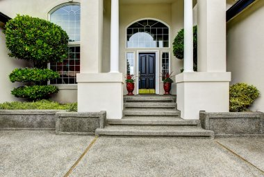 Luxury house entry way exterior with concrete floor porch.