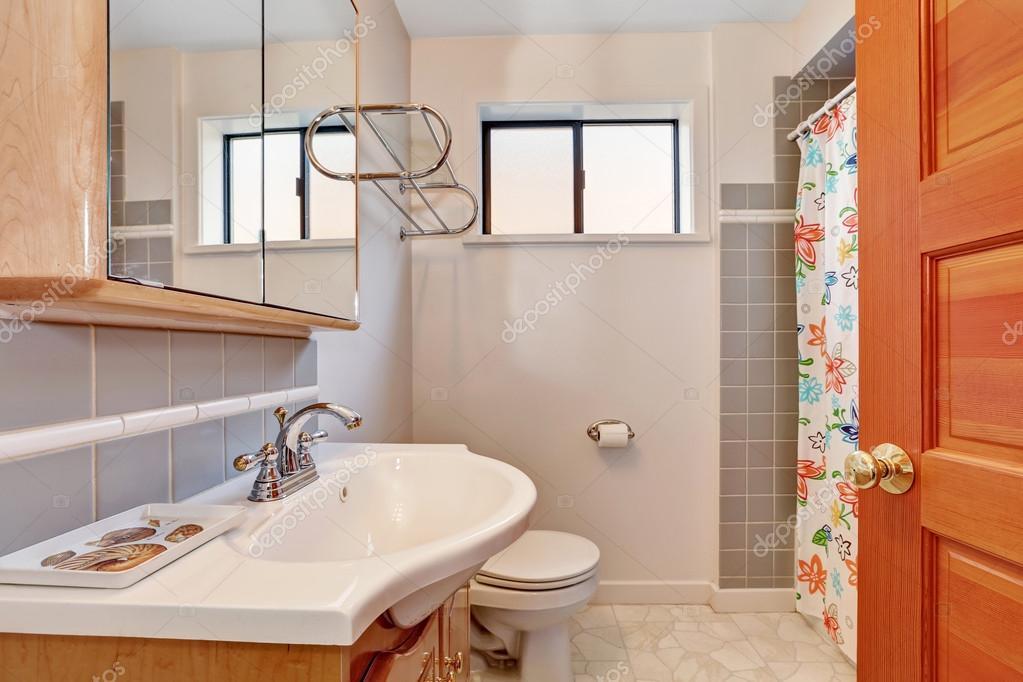 Interno bagno toni chiari con parete di piastrelle grigio trim