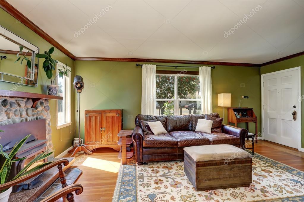 Groene muren woonkamer met stenen open haard en leren bank ...