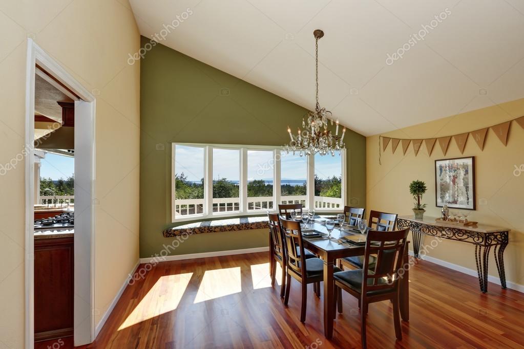 Elegant Dining Room With Contrast Olive Wall And Hardwood Floor Stockbild