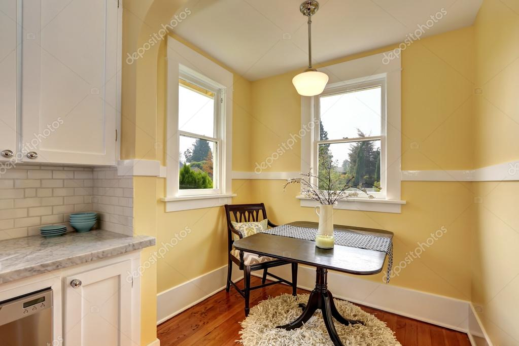small dining room area with yellow walls stock photo iriana88w